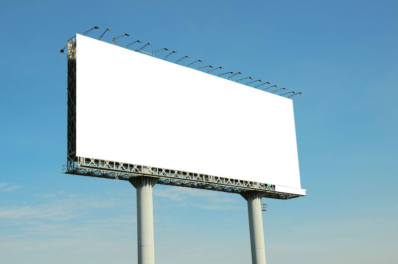 Low angle view of billboard against clear blue sky
