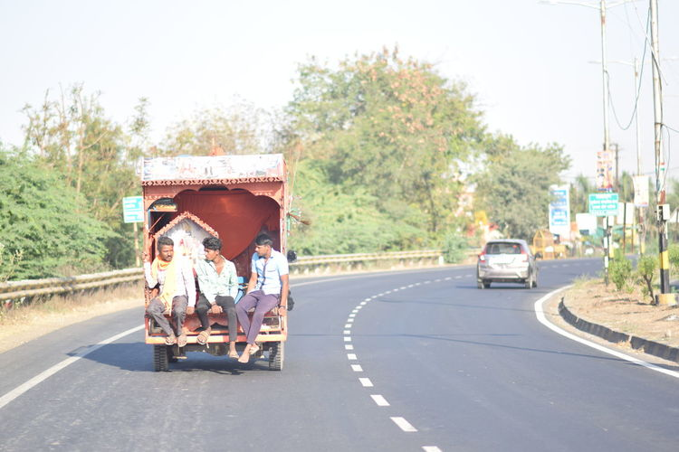 Rear view of vehicles on road against trees in city