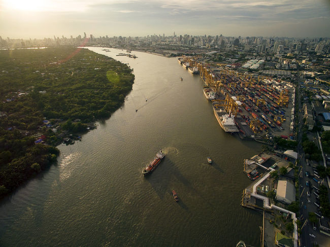 Aerial View Above the Bangkok Dockyard by the Chao Phraya River with Cargo Ships Waiting to be Upload and Offload Cargo Containers Bangkok Dockyard Cargo Ship ่Chao Phraya River Cityscape Container Container Ship Container Port Dockland Dockyard Panoramic Shipping Industry Aerial Photography Aerial View Architecture Cargo Loader Cargo Ships Evening Sky Marshland  Outdoors Shipping Docks Shipping Industry Tranquil Scene Transportation Water