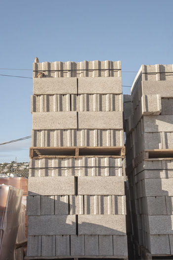 block for construction stored on pallet in a depot material Blocks Concrete Blocks Construction Wall Block Building Concrete Constructed Gray Material Outdoors Outside Pallet Stored
