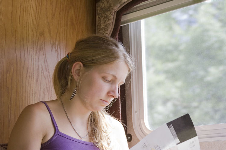 Young Woman Reading Magazine While Sitting By Window In Motor Home