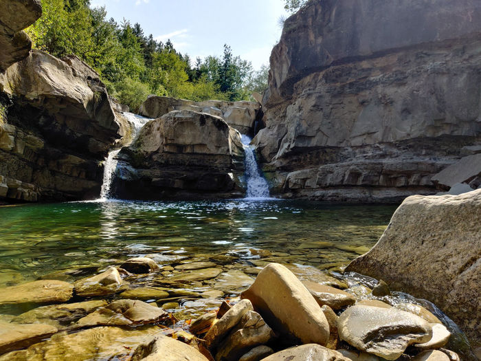 Scenic view of rocks in front of a waterfall against sky