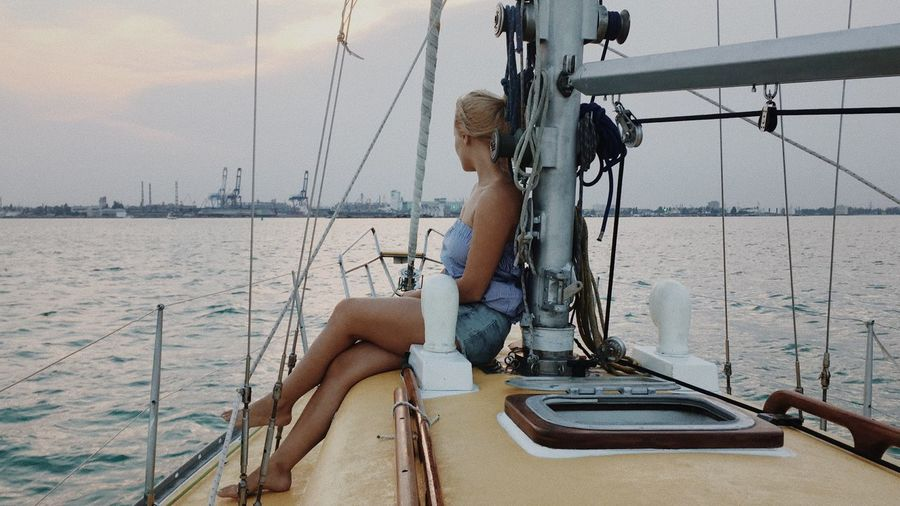 Young Woman Sitting On Sailboat
