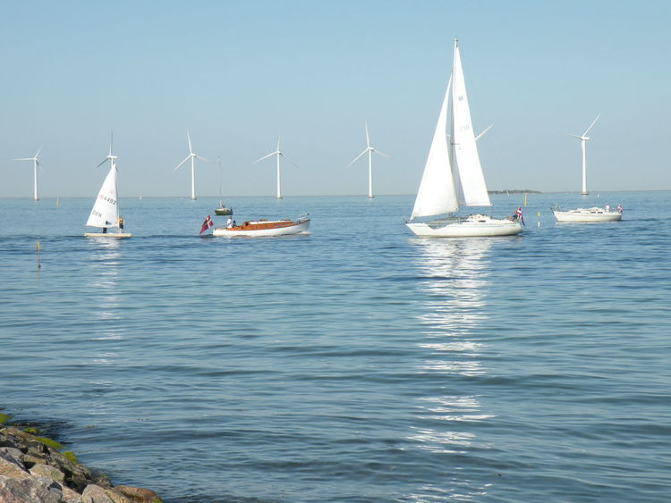 Sailboats and Windmills in Blue Sea in Spring - Nautical Vessel Sailboat Sea Sailing Mast Yacht Sailing Ship Travel Yachting Vacations Water Nature Day Ship Blue Sky Vindmøller Amager Strand Amager Windmill Wind Turbine - at Amager Beach on Amager Island in Denmark