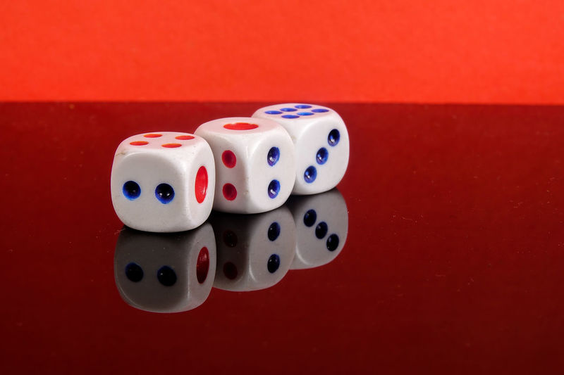 Stacked Dice on a red background Arts Culture And Entertainment Close-up Colored Background Cube Shape Dice Gambling Game Of Chance Group Of Objects High Angle View Indoors  Leisure Activity Leisure Games Luck No People Opportunity Red Relaxation Spotted Still Life Table White Color