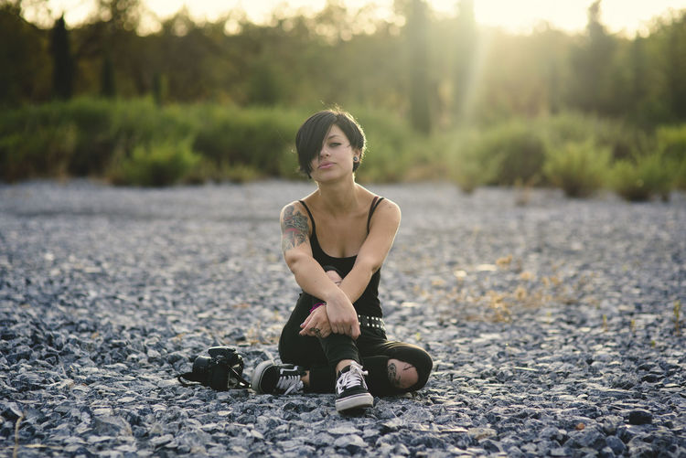 Beautiful young photographer woman wearing black clothes and short haircut sitting on the stone floor brunette girl thinking relaxed in the countryside. Beautiful Woman Day Exercising Focus On Foreground Front View Full Length Healthy Lifestyle Land Leisure Activity Lifestyles Nature One Person Outdoors Real People Sitting Sport Women Young Adult Young Women