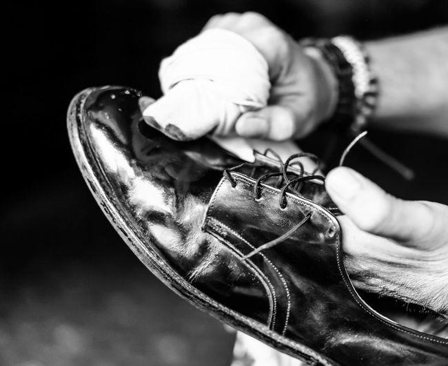 Cropped image of hands polishing shoe