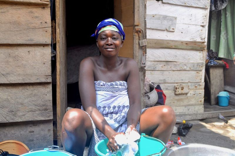 Portrait of smiling woman washing clothes while sitting at entrance