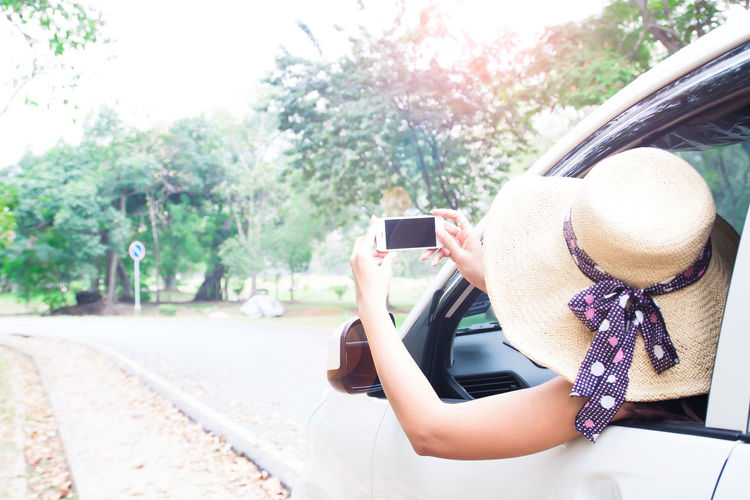 Woman Photographing With Mobile Phone While Traveling In Car