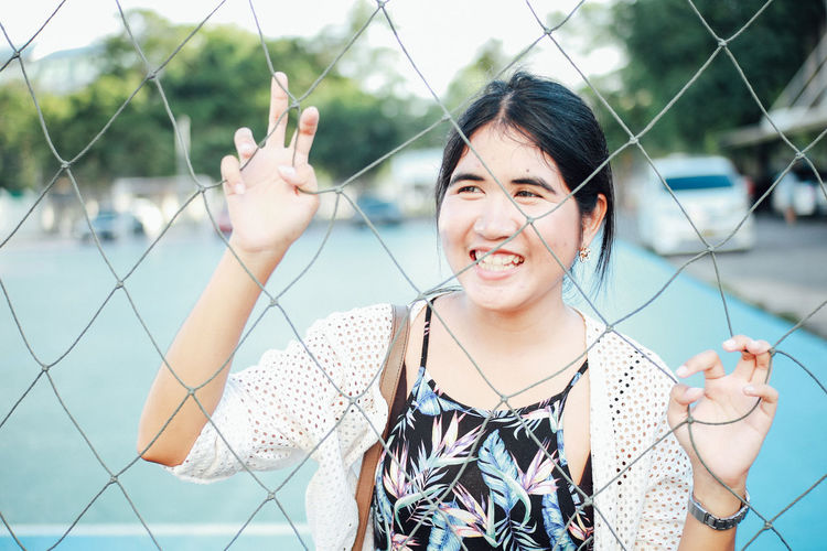 Smiling woman seen through net in court