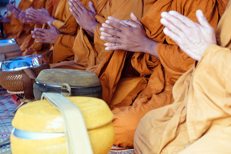 Midsection of monks praying while sitting by baskets