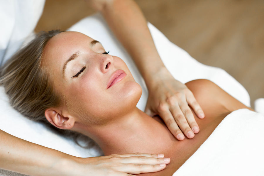 Young caucasian smiling woman receiving a head massage in a spa center with eyes closed. Female patient is receiving treatment by professional therapist. Blonde Relaxing Woman Beautiful Woman Beauty Blond Hair Closed Eyes Female Girl Physiotherapy Relax Spa Spa Center Young Adult Young Woman Young Women
