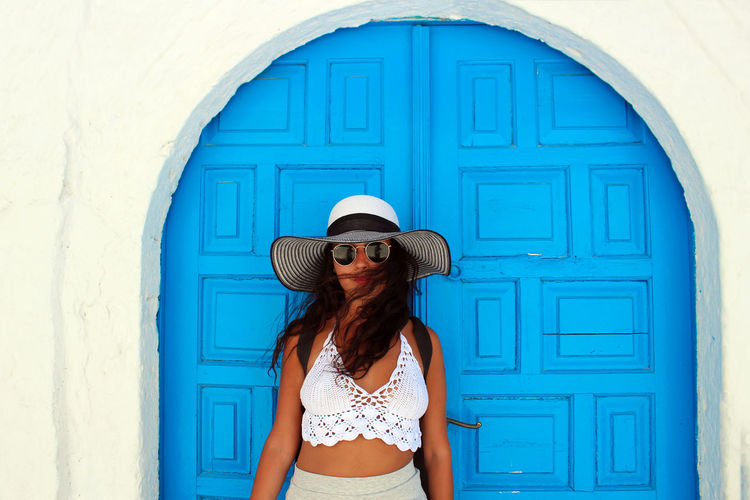Portrait of young woman wearing sunglasses standing against blue door