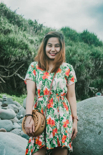 Portrait of smiling young woman standing against plants