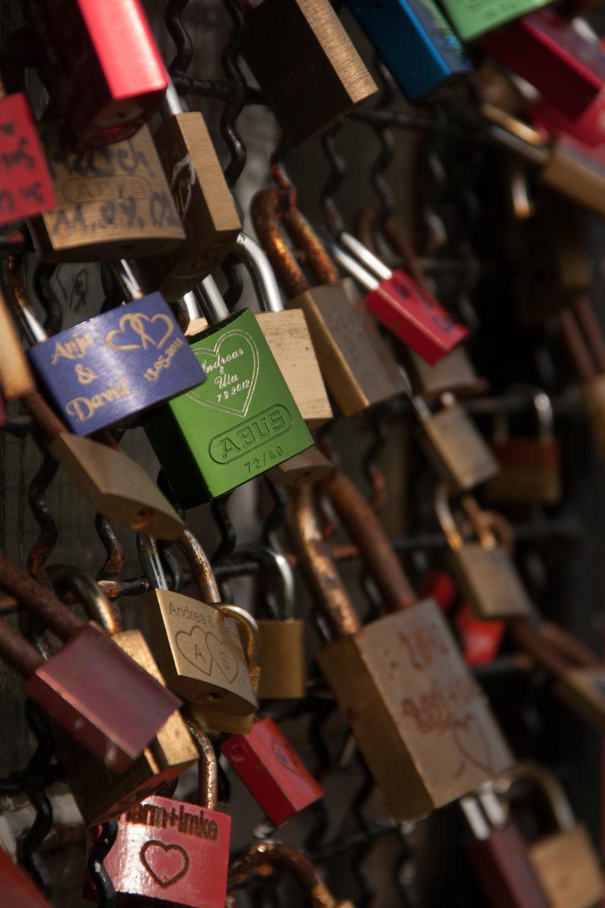 CLOSE-UP OF LOVE PADLOCKS HANGING ON HEART SHAPE