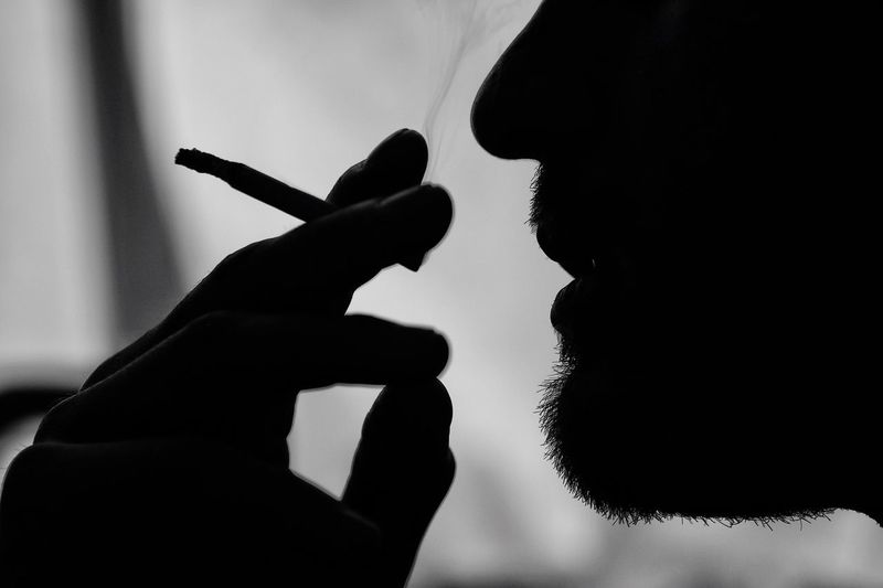 Cropped Image Of Silhouette Man Smoking Cigarette