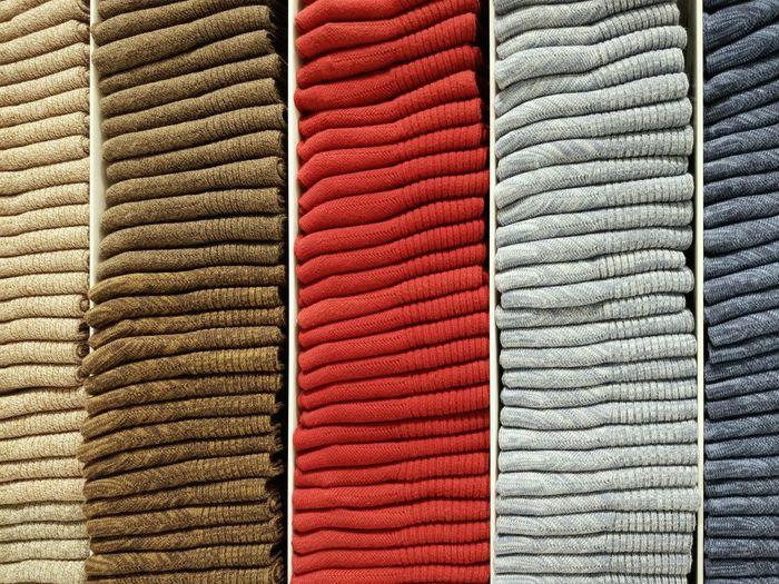 Full frame shot of folded textiles on shelves in store