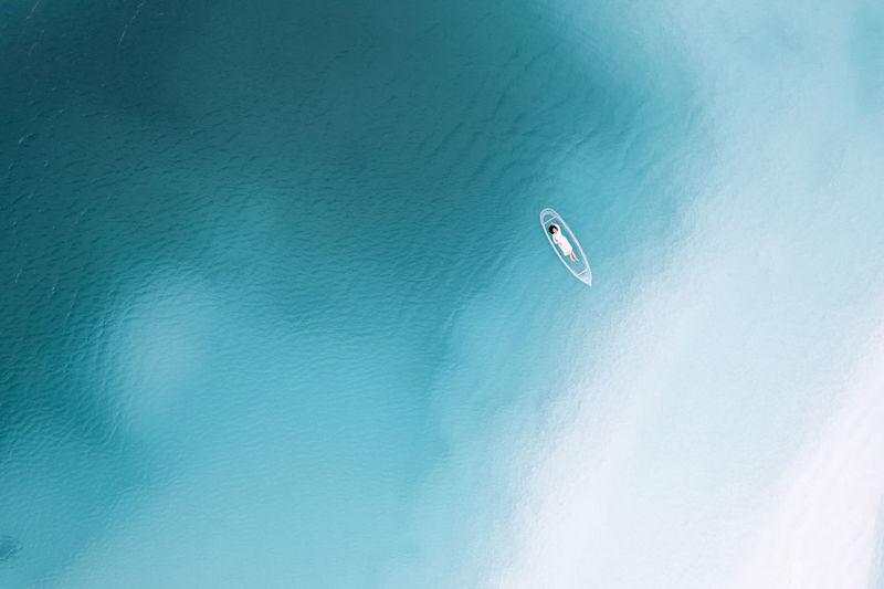 Kite flying over sea against blue sky