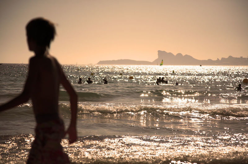 Golden hour at the beach, horizon over the sea, people bathing and swimming, silhouette of a kid