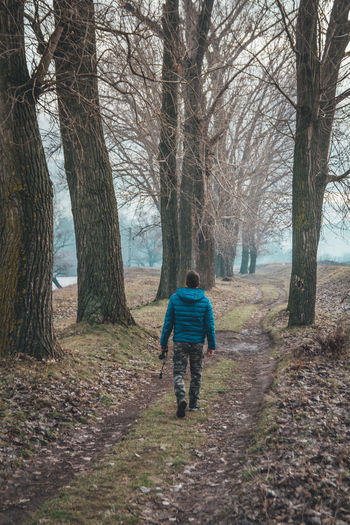 Young man birdwatching in forest, walking near river Tree One Person Full Length Rear View Land Tree Trunk Nature Bare Tree Trunk Leisure Activity Forest Walking Real People Men Winter Casual Clothing Footpath Outdoors WoodLand Warm Clothing Hood - Clothing Alone Birdwatching Binoculars
