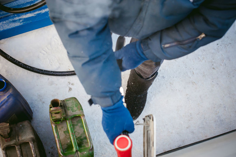 Low Section Of Man Filling Can With Fuel During Winter