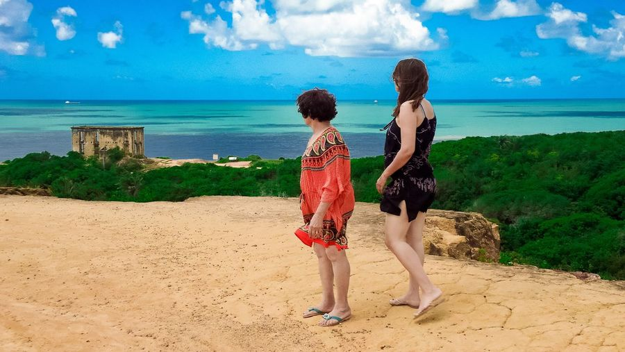 Full length of mother and daughter looking at sea against sky