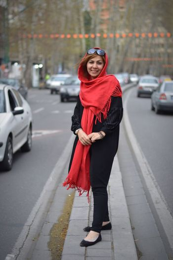 Portrait Of Smiling Mid Adult Woman Standing Amidst Road