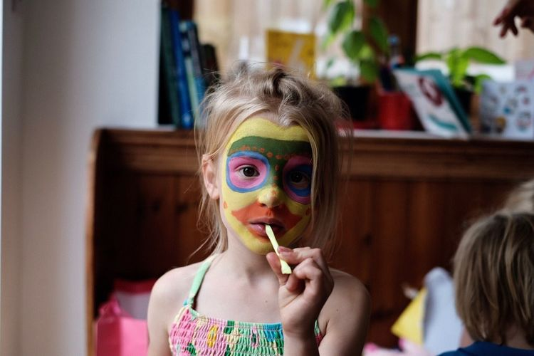 Girls Childhood Real People Child Fun Elementary Age Focus On Foreground One Person Bubble Wand Facepaint Facepainting Faces Of EyeEm Faces Party Face Of EyeEm Lifestyles Face Paint Multi Colored Indoors  Eyeglasses  Eating Blond Hair Children Only Day People
