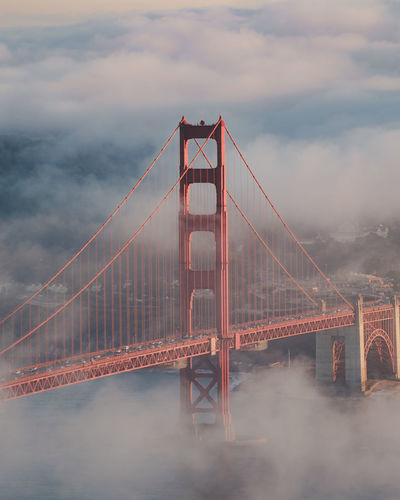 High angle view of golden gate bridge in city against cloudy sky