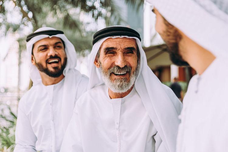 Smiling senior man with grandsons wearing dish dash sitting outdoors