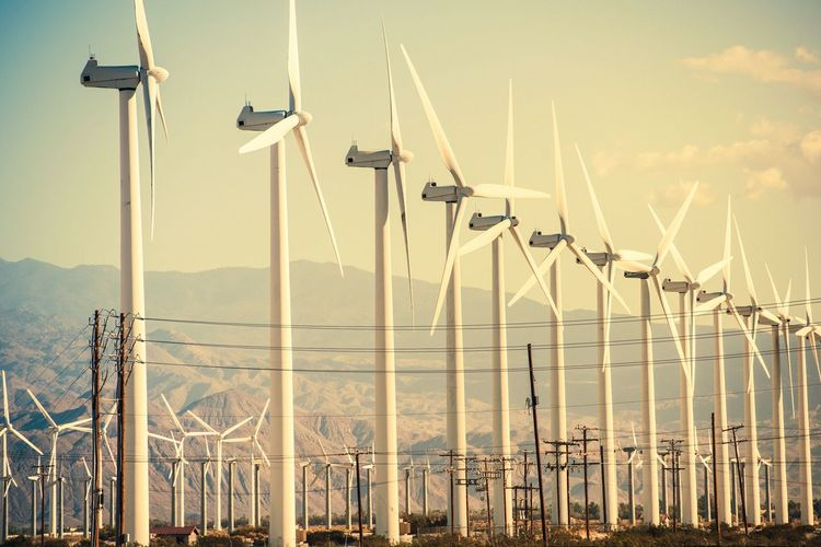 Windmills against mountains during sunset