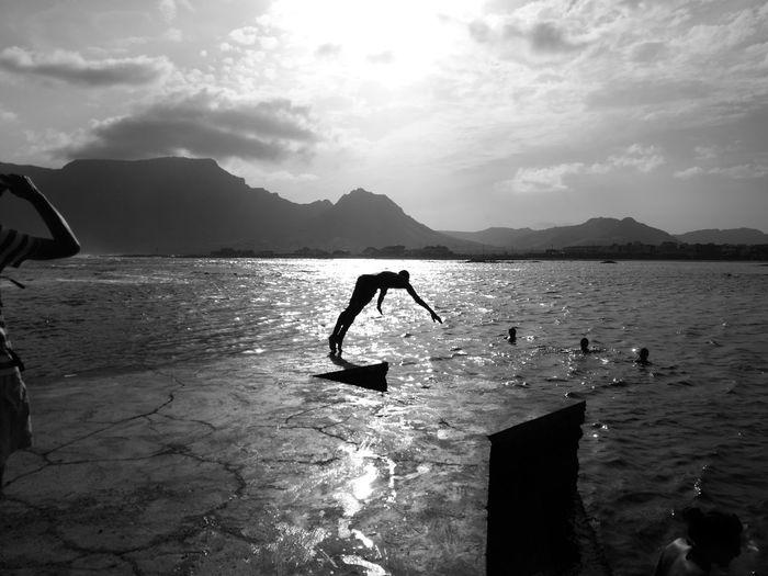 Silhouette Man Diving In Sea Against Sky