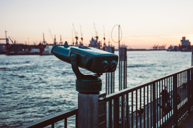 Close-up of coin-operated binoculars on pier by sea against sky