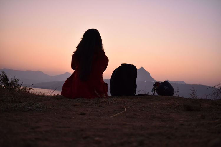 Rear View Of Woman Sitting On Mountain Against Sky During Sunset