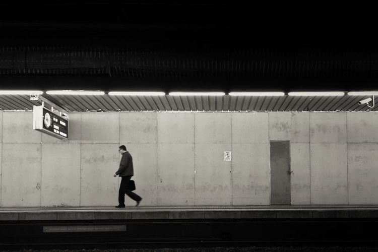 Side view of a man walking on railway station platform