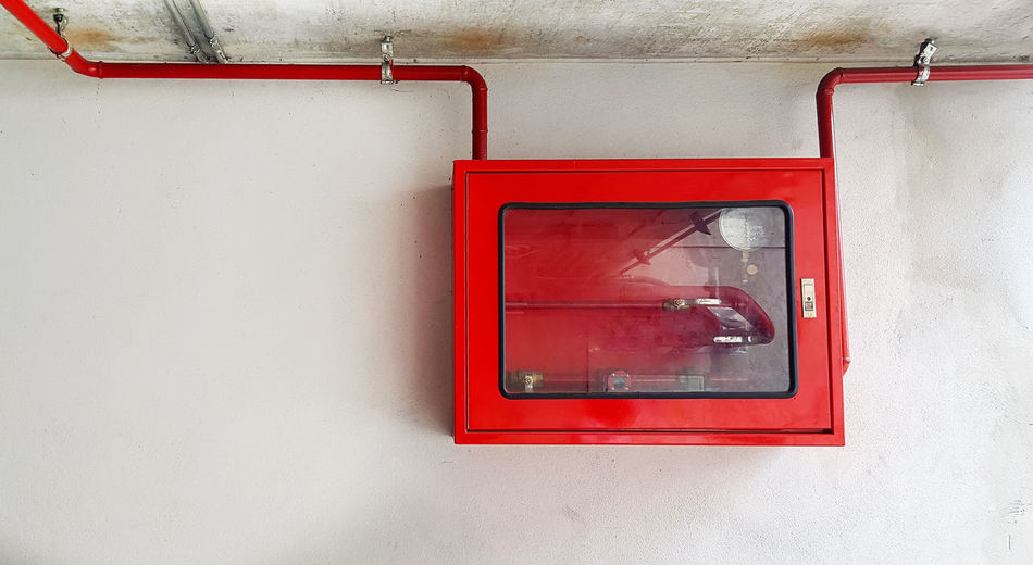 Close-up of red telephone on wall