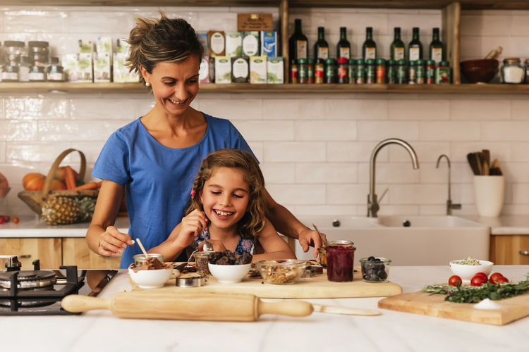 Mother Cooking Kitchen Daughter Mom Family Love Food Healthy Togetherness Having Fun Indoors  Copy Space Recipe Lifestyles Home People Caucasian Blonde Wood Childhood Positive Emotion Happiness Smiling Helper
