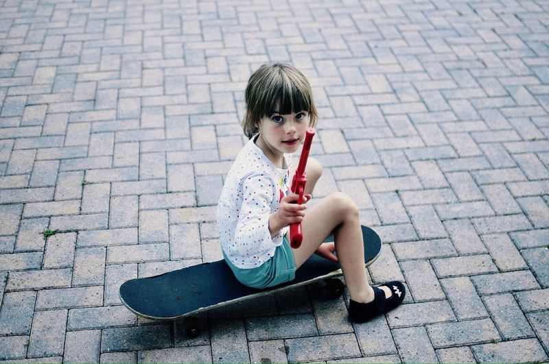 Portrait Of Girl Holding Toy Gun While Sitting On Skateboard
