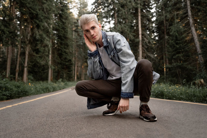 Portrait of young man crouching on road in forest