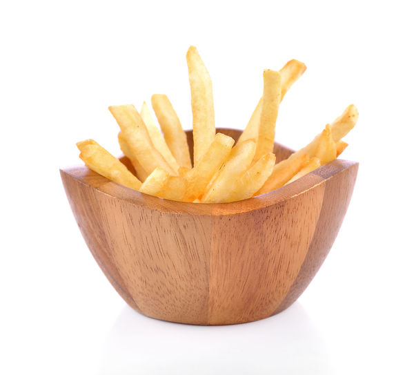 Close-up of fries on table against white background