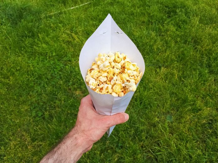 Cropped image of man holding popcorn in paper cone