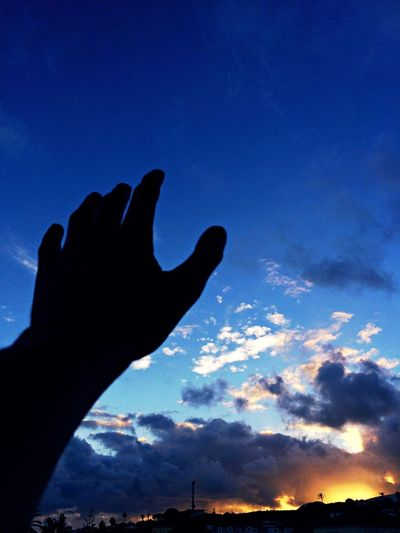 Silhouette of hand against sky at night