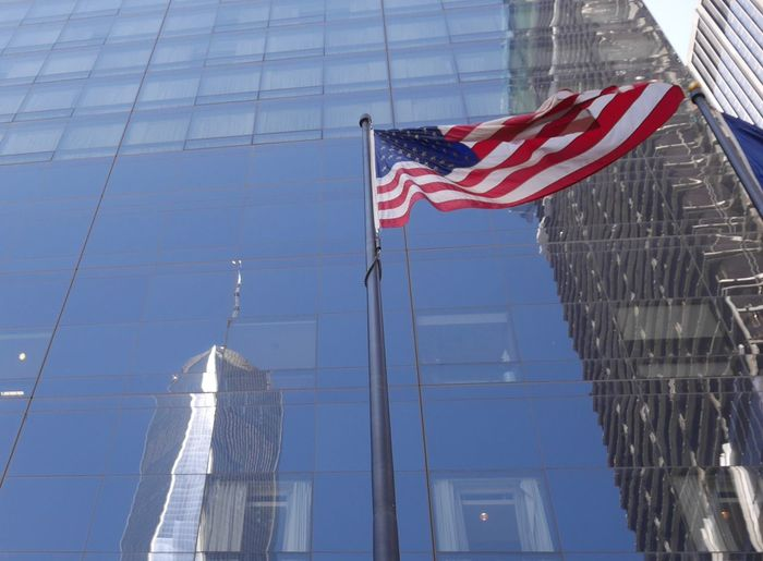 Low angle view of american flag against one world trade center reflection on glass building