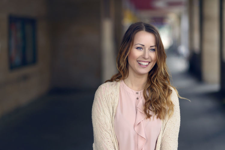 Portrait Of Smiling Woman Standing At Corridor