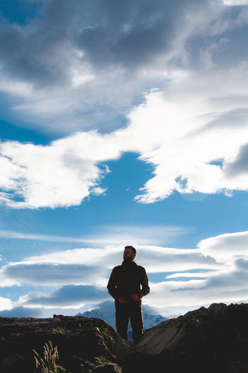 Man standing on rock against sky