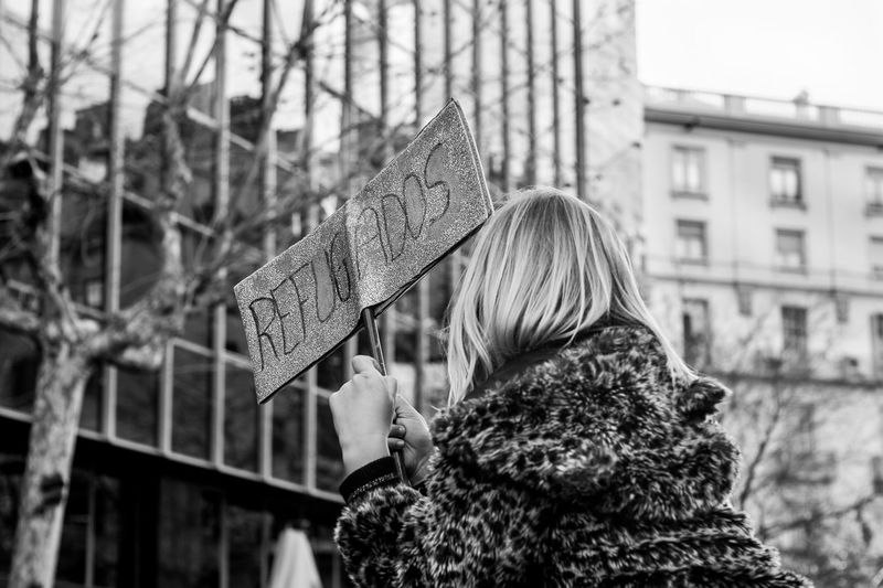 Rear view of a woman holding placard