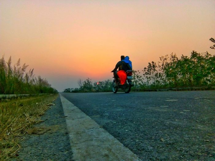 Rear view of man riding motorcycle on road against sky during sunset