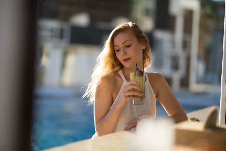 Adult Adults Only Beautiful Woman Close-up Day Drink Drinking Drinking Glass Drinking Straw Food And Drink Front View Holding Indoors  Leisure Activity One Person One Woman Only One Young Woman Only People Real People Refreshment Relaxation Sitting Young Adult Young Women