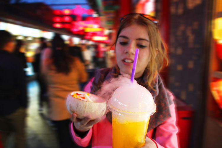 Young woman holding ice cream at night