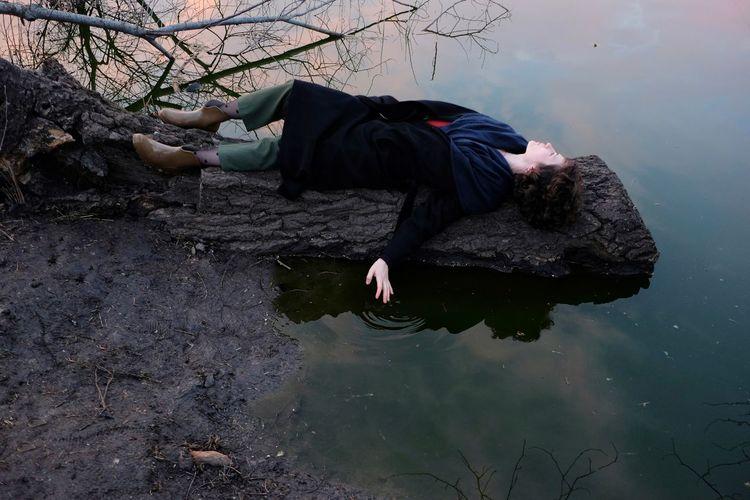 Full length of woman lying on fallen tree trunk by lake